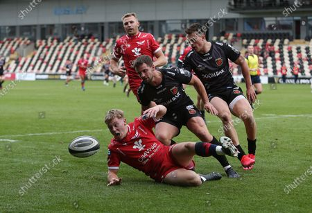 Sam Costelow of Scarlets is challenged by Joe Thomas and Jared Rosser of Dragons.