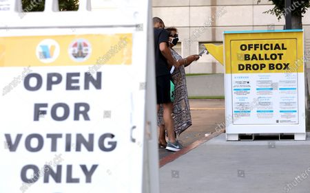 NORWALK, CA - OCTOBER 15, 2020 - Angela Marcano and her son Conrad drop off their ballots while voting early at the Los Angeles County Registrar of Voters-Recorders Office in Norwalk on October 15, 2020. The Registrar of Voters is open 7 days a week. This week it's open from 8 a.m,. to 5 p.m. Next week it's open from 8 a.m. to 7 p.m. (Genaro Molina / Los Angeles Times)