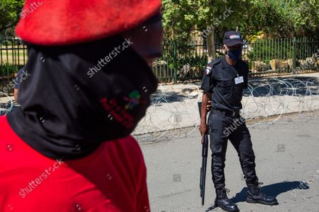 An armed guard stands on guard in front of a Julius Malema supporter outside the magistrates court during the protest. A tense standoff between white farmers and Black activists gripped the South African town of Senekal, as two men accused of killing a white farm manager were to appear in court. More than 100 police patrolled the area in front of the courthouse in the Free State province and used barbed wire to separate the rival groups.