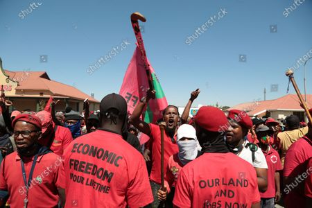 Members of the Economic Freedom Fighters (EFF) and Julius Malema supporters chant slogans outside the magistrates court during the protest. A tense standoff between white farmers and Black activists gripped the South African town of Senekal, as two men accused of killing a white farm manager were to appear in court. More than 100 police patrolled the area in front of the courthouse in the Free State province and used barbed wire to separate the rival groups.