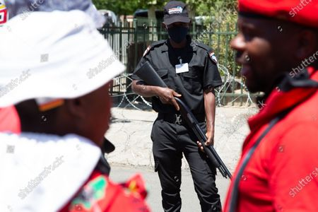 An armed guard stands on guard in front of Julius Malema supporters outside the magistrates court during the protest. A tense standoff between white farmers and Black activists gripped the South African town of Senekal, as two men accused of killing a white farm manager were to appear in court. More than 100 police patrolled the area in front of the courthouse in the Free State province and used barbed wire to separate the rival groups.