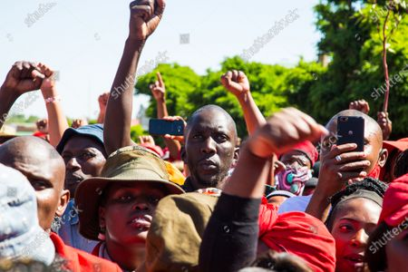 Members of the Economic Freedom Fighters (EFF) and Julius Malema supporters make gestures while standing outside the magistrates court during the protest. A tense standoff between white farmers and Black activists gripped the South African town of Senekal, as two men accused of killing a white farm manager were to appear in court. More than 100 police patrolled the area in front of the courthouse in the Free State province and used barbed wire to separate the rival groups.