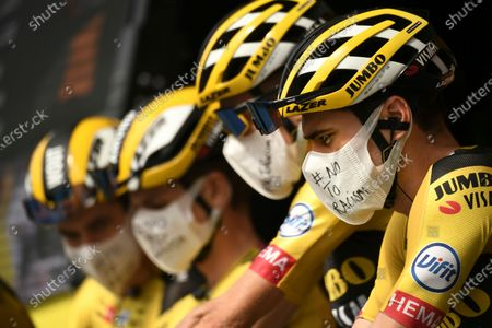 """Stock Picture of Netherland's Tom Dumoulin, right, and his teammates wear face masks reading """"No To Racism"""" as they arrive for the start of the twenty-first and last stage of the Tour de France cycling race over 122 kilometers (75.8 miles), from Mantes-La-Jolie to Paris, France"""