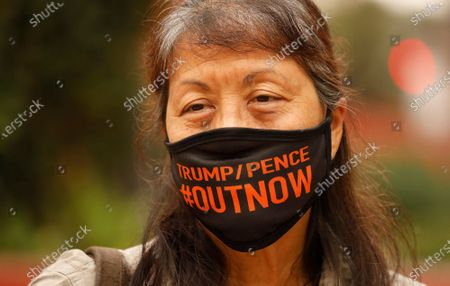 """Stock Picture of Jane Lee with Refuse Fascism watches as Refuse Fascism members began a 48-hour protest to denounce the Trump administration's assault on immigrants at Perswhiong Square in downtown Los Angeles on Friday morning. The demonstrators will be calling for L.A.-based U.S. Immigration and Customs Enforcement agents to cease local operations. """"We are in the midst of a rolling coup by the Trump/Pence regime,"""" says Andy Zee, a co-initiator of Refuse Fascism. """"Now is he time that we have to act to prevent them from carrying this all the way through."""" Pershing Square on Friday, Oct. 9, 2020 in Los Angeles, CA. (Al Seib / Los Angeles Times"""