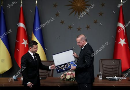 Turkish President Recep Tayyip Erdogan (R) gives order of state to Ukraine's President Volodymyr Zelensky (L) as they attend signing ceremony after their meeting in Istanbul, Turkey, 16 October 2020. Turkey and Ukraine signed a military agreement including Turkey's armed drones' sales and technology transfer to Ukraine.