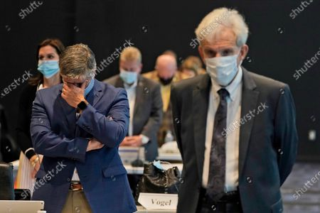 Stock Photo of Virginia State Sen. Ryan Newman, R-Bedford, left, listens to the prayer along with State Sen. Richard Saslaw, D-Fairfax, right, during a special session of the Virginia Senate in a temporary location at the Science Museum of Virginia in Richmond, Va