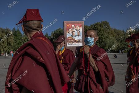 Tibetan nuns walk past a monument showing Chinese leaders, clockwise from top, Mao Zedong, Deng Xiaoping, Hu Jintao, current Chinese President Xi Jinping, and Jiang Zemin as they visit the Potala Palace Square in Lhasa, Tibet Autonomous Region, China, 15 October 2020 (issued 16 October 2020). The visit to Tibet for journalists is a government-organised media tour focused on a poverty alleviation program. Tibet is considered one of China's poverty-stricken areas. The Chinese government plans to eradicate extreme poverty by the end of 2020. The famous Potala Palace used to be the main residence of the Dalai Lama but is now preserved as a museum and world heritage site.