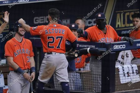 Houston Astros' Jose Altuve is congratulated after scoring on the RBI single by Carlos Correa during the fifth inning in Game 6 of a baseball American League Championship Series against the Tampa Bay Rays, in San Diego