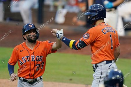 Houston Astros' Jose Altuve (27) celebrates with Carlos Correa after scoring on an RBI single by Michael Brantley during the seventh inning in Game 6 of a baseball American League Championship Series, in San Diego