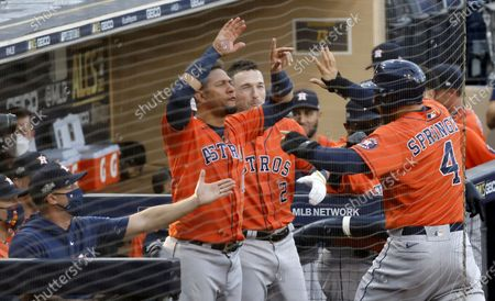 Houston Astros center fielder George Springer (R) celebrates with his teammates at their dugout after scoring on teammate Houston Astros second baseman Jose Altuve's (not pictured) RBI double to left field in the top of the fifth inning of the MLB American League Championship Series playoff baseball game six between the Houston Astros and Tampa Bay Rays at Petco Park in San Diego, California, USA, 16 October 2020.