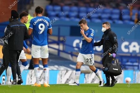 Everton's Seamus Coleman, second right, leaves the match with an injury as substitute Everton's Ben Godfrey, back left, comes on in his place during the English Premier League soccer match between Everton and Liverpool at Goodison Park stadium, in Liverpool, England