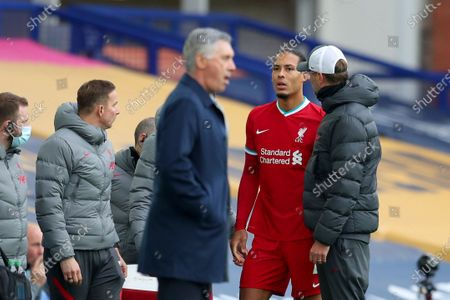Liverpool's manager Jurgen Klopp, right, checks on Liverpool's Virgil van Dijk, second right, as he leaves the match with an injury during the English Premier League soccer match between Everton and Liverpool at Goodison Park stadium, in Liverpool, England