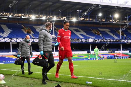 Liverpool's Virgil van Dijk leaves the match with an injury during the English Premier League soccer match between Everton and Liverpool at Goodison Park stadium, in Liverpool, England
