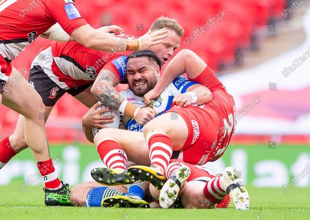 Leeds's Konrad Hurrell is tackled by Salford's James Greenwood and Kevin Brown.