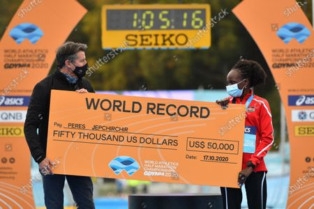 IAAF President Sebastian Coe (L) presents a check over 50,000 USD to Peres Jepchirchir (R) from Kenya during the International Association of Athletics Federations (IAAF) Women's World Half Marathon Championships 2020 in Gdynia, northern Poland, 17 October 2020. Peres Jepchirchir has set a new women's world record.