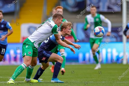 Millwall defender Shaun Hutchinson (4) tussles with Wycombe Wanderers forward Alex Samuel (25) during the EFL Sky Bet Championship match between Wycombe Wanderers and Millwall at Adams Park, High Wycombe