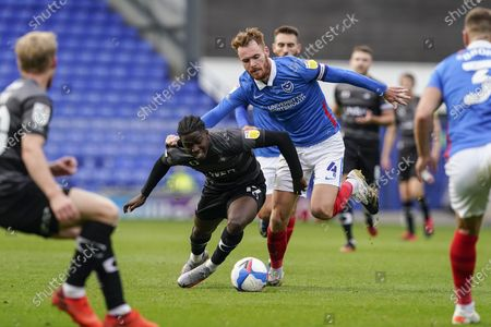 Stock Image of Tom Naylor of Portsmouth tackles Taylor Richards of Doncaster Rovers during the EFL Sky Bet League 1 match between Portsmouth and Doncaster Rovers at Fratton Park, Portsmouth