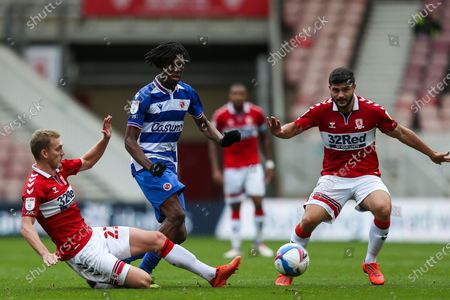 Stock Image of Middlesbrough midfielder George Saville (22) slides in on Reading midfielder Ovie Ejaria (14) as Middlesbrough midfielder Sam Morsy (5) watches on during the EFL Sky Bet Championship match between Middlesbrough and Reading at the Riverside Stadium, Middlesbrough