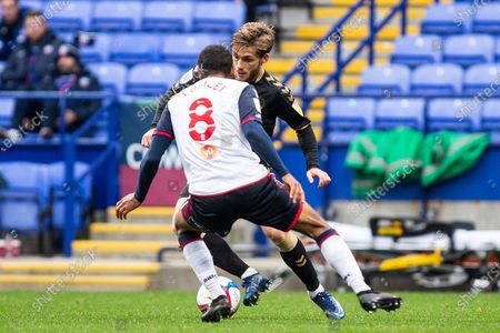 Oldham Athletic forward Conor McAleny (18) tackled by Bolton Wanderers midfielder Brandon Comley (8) during the EFL Sky Bet League 2 match between Bolton Wanderers and Oldham Athletic at the University of  Bolton Stadium, Bolton