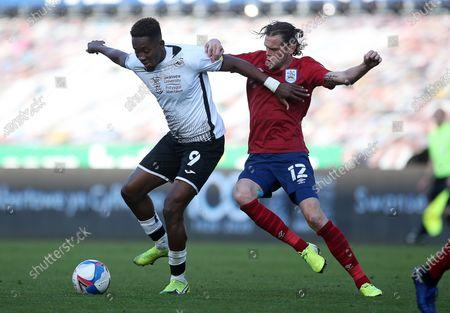 Jamal Lowe of Swansea City is tackled by Richard Stearman of Huddersfield Town.