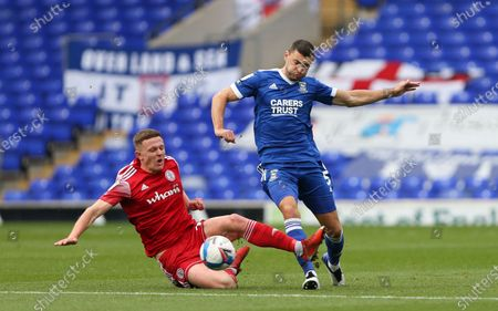 James Wilson of Ipswich Town passes the ball under pressure from Colby Bishop of Accrington Stanley