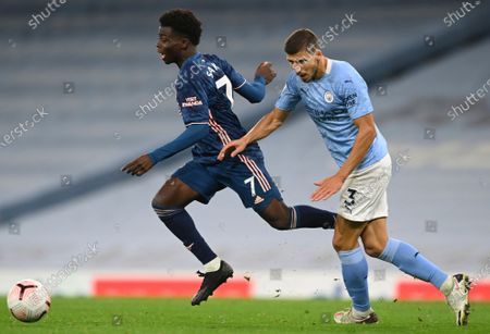 Arsenal's Bukayo Saka, left, duels for the ball with Manchester City's Ruben Dias during the English Premier League soccer match between Manchester City and Arsenal at the Etihad stadium in Manchester, England
