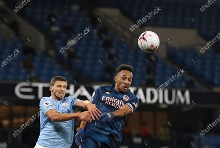 Manchester City's Ruben Dias, left, jumps for the ball with Arsenal's Pierre-Emerick Aubameyang during the English Premier League soccer match between Manchester City and Arsenal at the Etihad stadium in Manchester, England