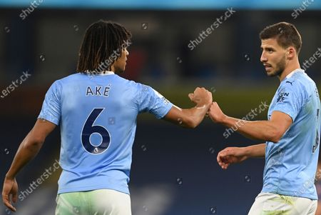 Manchester City's Nathan Ake, left, fist bumps with Manchester City's Ruben Dias at the end of the English Premier League soccer match between Manchester City and Arsenal at the Etihad stadium in Manchester, England
