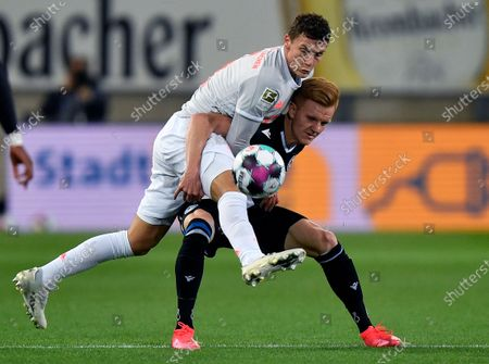 Bayern's Benjamin Pavard, left, and Arminia's Christian Gebauer, right, challenge for the ball during the German Bundesliga soccer match between Arminia Bielefeld and FC Bayern Munich in Bielefeld, Germany