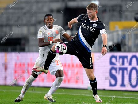 Bayern's David Alaba, left, and Arminia's Fabian Klos, right, challenge for the ball during the German Bundesliga soccer match between Arminia Bielefeld and FC Bayern Munich in Bielefeld, Germany