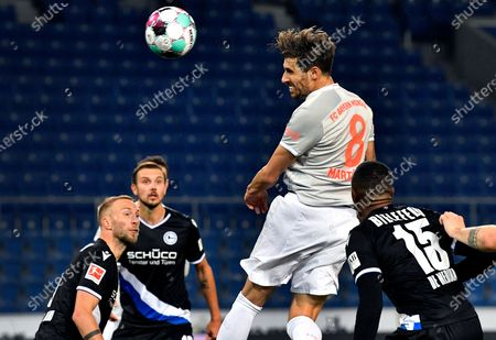 Bayern's Javi Martinez, center, goes for a header during the German Bundesliga soccer match between Arminia Bielefeld and FC Bayern Munich in Bielefeld, Germany