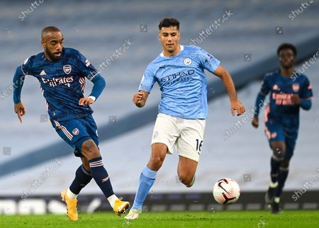 Alexandre Lacazette (L) of Arsenal in action against Rodrigo (C) of Manchester City during the English Premier League soccer match between Manchester City and Arsenal FC in Manchester, Britain, 17 October 2020.
