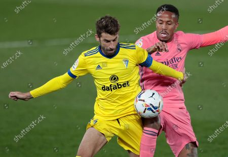 Stock Image of Cadiz's Jose Mari, left, and Real Madrid's Eder Militao fight for possession during the Spanish La Liga soccer match between Real Madrid and Cadiz at the Alfredo di Stefano stadium in Madrid, Spain