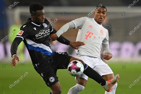 Bielefeld's Anderson Lucoqui (L) in action against Bayern's Douglas Costa (R) during the German Bundesliga match between Arminia Bielefeld and Bayern Muenchen at SchuecoArena in Bielefeld, Germany, 17 October 2020.