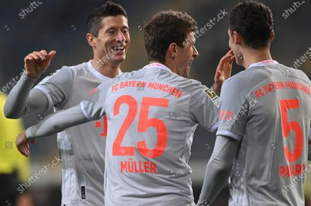 Bayern's Thomas Mueller (C) celebrates his 0-4 goal with Bayern's Robert Lewandowski (L) and Bayern's Benjamin Pavard (R) during the German Bundesliga match between Arminia Bielefeld and Bayern Muenchen at SchuecoArena in Bielefeld, Germany, 17 October 2020.
