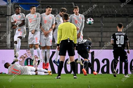 Bayern's Douglas Costa (L) lies on the pitch as part of the Bayern wall during the German Bundesliga match between Arminia Bielefeld and Bayern Muenchen at SchuecoArena in Bielefeld, Germany, 17 October 2020.