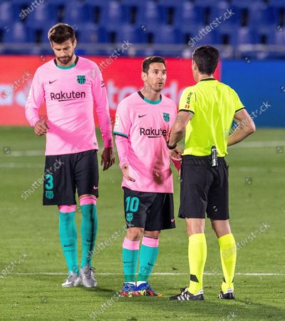 FC Barcelona players Lionel Messi (C) and Gerard Pique (L) argue with referee Soto Grado (R) during the Spanish La Liga soccer match between Getafe CF and FC Barcelona at Antonio Perez Coliseum in Getafe, near Madrid, Spain, 17 October 2020.