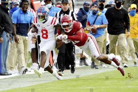 Mississippi receiver Elijah Moore (8) is knocked out of bounds by Arkansas defensive back Myles Mason during the second half of an NCAA college football game, in Fayetteville, Ark