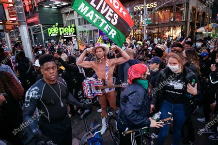 The Naked Cowboy flexes for a photo while surrounded by activists rallying against police misconduct in the shooting of Breonna Taylor, in New York. Taylor, a 26-year-old unarmed African-American woman, was fatally shot as police conducted a no-knock warrant at her home in Louisville, Kentucky in March