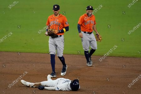 Tampa Bay Rays Randy Arozarena lies on second base after he was forced out by Houston Astros shortstop Carlos Correa during the third inning in Game 7 of a baseball American League Championship Series, in San Diego. At right is Houston Astros second baseman Jose Altuve