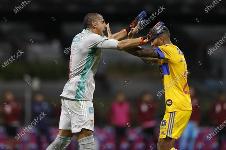 Tigres' goalkeeper Nahuel Guzman, left, celebrates with teammate Francisco Meza after Cruz Azul's Jonathan Rodriguez failed to score a penalty kick during a Mexican soccer league match at Azteca stadium in Mexico City, . The match was played without fans as a precaution against the coronavirus