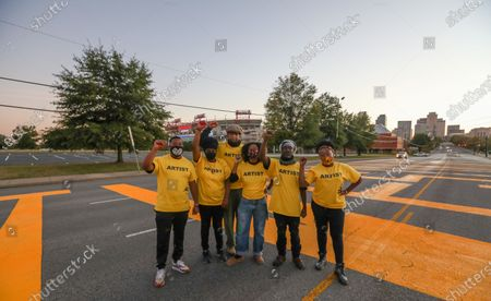 (L-R) Christian Green, Stacia Thomas, Thaxton waters, Megan Jordan, Charlie Huddleston and Elise Kendrick paint a Black Lives Matter mural on the street outside the Titans Stadium