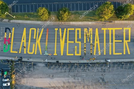 A group of artists and volunteers paint a Black Lives Matter mural on the street outside the Titans Stadium