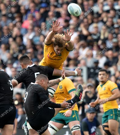 New Zealand's Aaron Smith kicks the ball as Australia's Ned Hanigan attempts to charge it down during the second Bledisloe Rugby test between the All Blacks and the Wallabies at Eden Park in Auckland, New Zealand