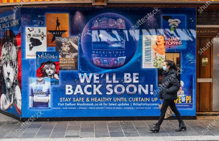 Stock Picture of A woman wearing a face mask walks past a new signage with 'We'll be back soon' on the Sondheim theatre completed after Producer Cameron Mackintosh announced that Les Miserables is set to come back to London's West End by Christmas with tickets going on sale soon after having shut due to the UK entering lockdown.