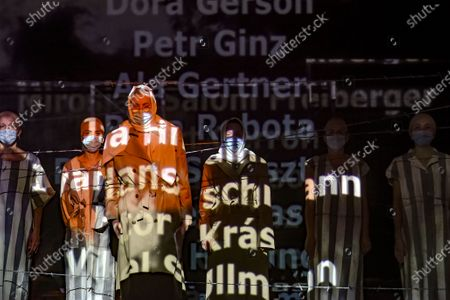"""Stock Photo of Names of victims scroll on a mesh at the Jewish State Theatre as actresses perform wearing face masks for protection against COVID-19 infection, during the rehearsals for premiere of the """"The Beautiful Days of My Youth"""" play, based on the diary of Romanian Jewish Holocaust survivor Ana Novac, in Bucharest, . Maia Morgenstern, second from left, head of the Jewish State Theater and a Romanian Jewish actress best known for playing Mary in Mel Gibson's controversial 2004 movie """"The Passion of the Christ,"""" described the play's staging in an interview with The Associated Press as an """"all-feminine project"""