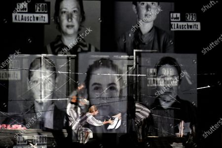 """Portraits of Auschwitz death camp prisoners are displayed on a mesh as actresses of the Jewish State Theatre, perform during the premiere of the """"The Beautiful Days of My Youth"""" play, based on the diary of Romanian Jewish Holocaust survivor Ana Novac, in Bucharest, . Maia Morgenstern, head of the Jewish State Theater and a Romanian Jewish actress best known for playing Mary in Mel Gibson's controversial 2004 movie """"The Passion of the Christ,"""" described the play's staging in an interview with The Associated Press as an """"all-feminine project"""