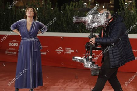 "Man with a camera wrapped up with plastic films Valeria Bruni Tedeschi posing for photographers on the red carpet for the movie ""Ete 85"" (Summer 85) at the Rome Film Fest, in Rome"