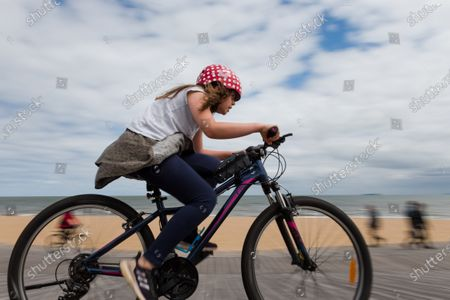 A girl is seen riding her bike along the St Kilda foreshore during COVID-19 in St Kilda, Australia. Premier Daniel Andrews is under mounting pressure to ease restrictions in line with NSW, despite this, in his much anticipated press conference earlier on Sunday, the Premier only slightly lifted the worlds longest and strictest lockdown. Business saw no relief with only a hint of easing to come in two weeks.