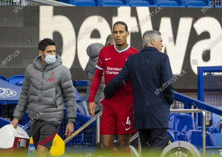 Liverpool's injured Virgil van Dijk (C) walks past Everton's manager Carlo Ancelotti (R) during the Premier League match between Everton FC and Liverpool FC at Goodison Park in Liverpool, Britain, on Oct. 17, 2020. The game ended in a 2-2 draw.